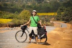 Turista da bicicleta na estrada rural Fotografia de Stock