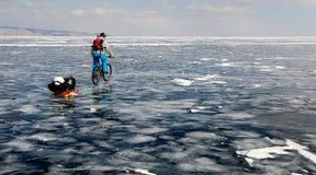 Turista da bicicleta no lago congelado Imagem de Stock