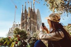 Turista da jovem mulher na frente do marco famoso de Sagrada Familia em Barcelona foto de stock