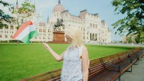 Turista da jovem mulher que levanta com a bandeira húngara no fundo do parlamento no turismo de Budapest em Europa filme