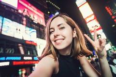 Turista da jovem mulher que ri e que toma a foto do selfie em New York City, Manhattan, Times Square Imagens de Stock