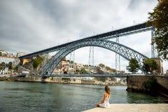 Turista da jovem mulher que senta-se com grande opinião da arquitetura da cidade em Porto c imagens de stock