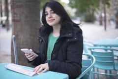 Turista da jovem mulher que senta-se em um café fora, usando o smartphone, guardando o mapa do destino fotos de stock