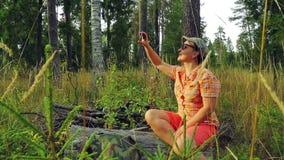 Turista da menina nos óculos de sol e em um boné de beisebol na floresta em um dia ensolarado que senta-se em uma árvore caída e  vídeos de arquivo