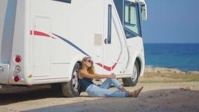 Turista da menina perto de seu reboque no estacionamento perto do mar video estoque