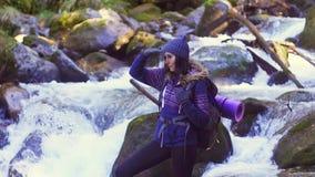 Turista da menina que está em uma pedra nas madeiras perto de um rio da montanha e que olha na distância, mo lento filme