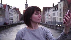 Turista da menina que faz o selfie no smartphone no por do sol em Bruges Bélgica vídeos de arquivo