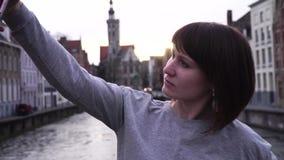 Turista da menina que faz o selfie no smartphone no por do sol em Bruges Bélgica Movimento lento video estoque