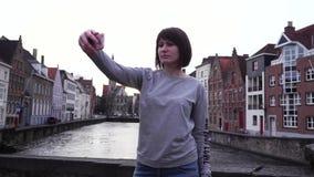 Turista da menina que faz o selfie no smartphone no por do sol em Bruges Bélgica Movimento lento filme