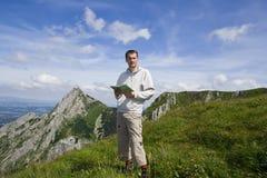 Turista da montanha com o mapa sobre o céu azul Foto de Stock Royalty Free
