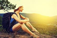 Turista da mulher com um assento da trouxa, descansando em uma parte superior da montanha em uma rocha na viagem Imagem de Stock Royalty Free