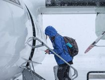 Turista da mulher que anda através de um blizzard aos aviões fotos de stock royalty free