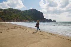 Turista da mulher que anda no litoral e que olha ao mar tormentoso fotos de stock