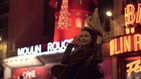 Turista da mulher que levanta para fazer o melhor tiro perto do vermelho de Moulin na noite Paris filme