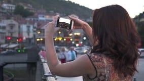 Turista da mulher que toma a foto pelo telefone celular da cidade velha com luzes de rua filme