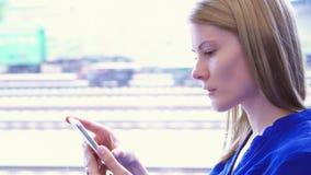 Turista da mulher que viaja no trem Usando seu smartphone, consultando, lendo a notícia, conversando com amigos filme