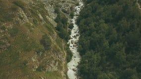 Turista da vista aérea que viaja ao longo do rio rápido na montanha Escalando uma montanha filme