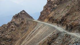 Turista de la bicicleta en el camino de la montaña Foto de archivo libre de regalías