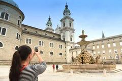 Turista de la chica joven que toma imágenes en el teléfono móvil en Residenzpl fotos de archivo