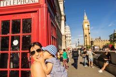 Turista de la madre y del bebé del viaje de Londres por Big Ben y la cabina de teléfono roja Imagen de archivo