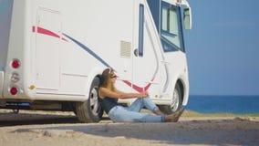 Turista de la muchacha cerca de su remolque en el aparcamiento cerca del mar almacen de metraje de vídeo