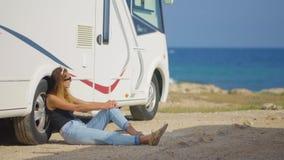 Turista de la muchacha cerca de su remolque en el aparcamiento cerca del mar metrajes