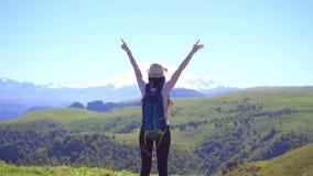 Turista de la muchacha con la mochila que gesticula el éxito en la montaña, concepto del ganador almacen de metraje de vídeo