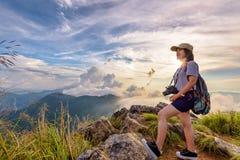 Turista de la muchacha en las montañas en la puesta del sol Fotos de archivo libres de regalías