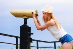 Turista de la mujer con el sombrero del sol que mira a través del telescopio Fotos de archivo libres de regalías