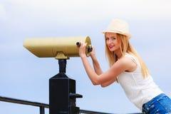 Turista de la mujer con el sombrero del sol que mira a través del telescopio Imagen de archivo