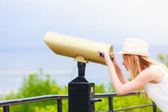 Turista de la mujer con el sombrero del sol que mira a través del telescopio Fotos de archivo