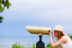Turista de la mujer con el sombrero del sol que mira a través del telescopio Fotografía de archivo