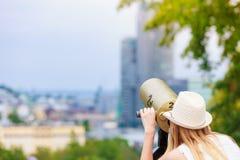 Turista de la mujer con el sombrero del sol que mira a través del telescopio Imagenes de archivo
