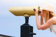 Turista de la mujer con el sombrero del sol que mira a través del telescopio Fotografía de archivo libre de regalías
