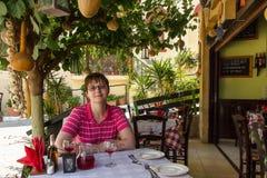 Turista de la mujer en el restaurante o el taverna griego Fotos de archivo
