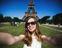 Turista de la mujer en la torre Eiffel que sonríe y que hace Imágenes de archivo libres de regalías