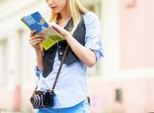 Turista de la mujer joven con el mapa en la ciudad Fotografía de archivo