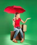 Turista de la mujer joven con el paraguas y una maleta Imagen de archivo libre de regalías