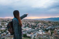 Turista de la mujer joven con el punto álgido que muestra la mano en la puesta del sol sobre la ciudad de Goreme en Turquía Cappa Imágenes de archivo libres de regalías
