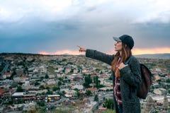 Turista de la mujer joven con el punto álgido que muestra la mano en la puesta del sol sobre la ciudad de Goreme en Turquía Cappa Foto de archivo libre de regalías