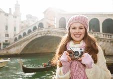 Turista de la mujer joven con la cámara retra de la foto cerca del puente de Rialto Foto de archivo