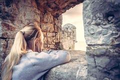 Turista de la mujer joven que mira en la distancia a través de ventana de piedra antigua en fortaleza vieja durante puesta del so Imagen de archivo