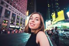 Turista de la mujer joven que ríe y que toma la foto del selfie en New York City, Manhattan, Times Square Foto de archivo libre de regalías