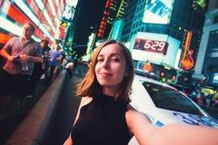 Turista de la mujer joven que ríe y que toma la foto del selfie en New York City, Manhattan, Times Square Imagenes de archivo