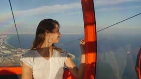 Turista de la mujer joven que se sienta en teleférico en la manera al top de la montaña almacen de video