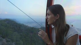 Turista de la mujer joven que se sienta en teleférico mientras que se baja almacen de video