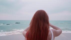 Turista de la mujer joven que toma las imágenes de la puesta del sol por el océano almacen de metraje de vídeo