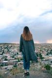 Turista de la mujer joven de un punto álgido que mira la puesta del sol sobre la ciudad de Goreme en Cappadocia en Turquía y el s Foto de archivo