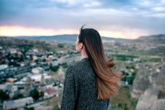 Turista de la mujer joven de un punto álgido que mira la puesta del sol sobre la ciudad de Goreme en Cappadocia en Turquía y el s Imagen de archivo libre de regalías
