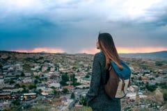 Turista de la mujer joven de un punto álgido que mira la puesta del sol sobre la ciudad de Goreme en Turquía y el sueño Cappadoci Imagen de archivo